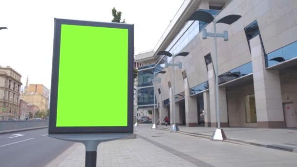Billboard se zelenou obrazovkou se nachází na ulici, v blízkosti kancelářské budovy