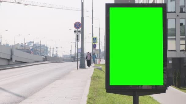 Billboard se zelenou obrazovkou umístěnou na ul. Nedaleko je silniční most, na kterém se pohybují automobily