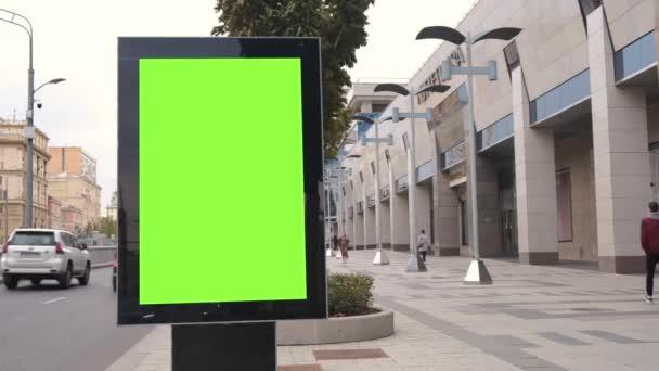 Zöld képernyős hirdetőtábla található egy forgalmas utcán. Az autók nagy sebességgel haladnak.