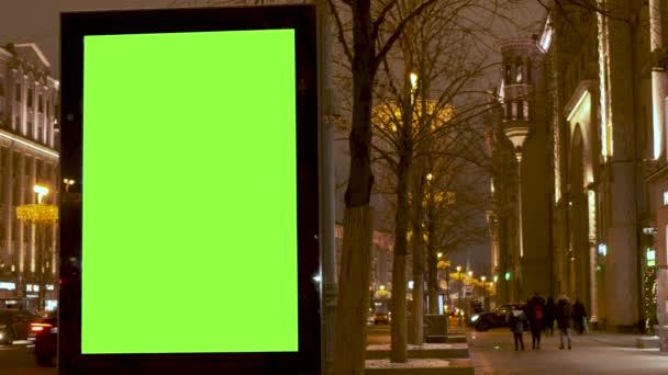 Zelený billboard umístěný na chodníku, po kterém lidé chodí, vedle rušné ulice. Auta se pohybují večer.