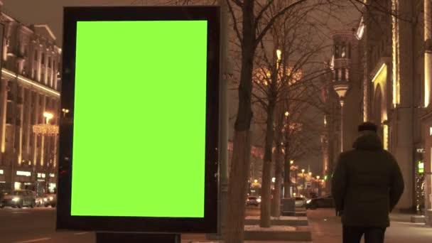 Egy zöld képernyős hirdetőtábla található a járdán, amelyen az emberek sétálnak, egy forgalmas utca mellett. Az autók este mozognak..