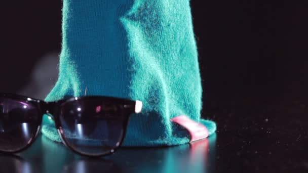 Winter fashion. Knitted hat and sunglasses. Blue woolen knitted cap