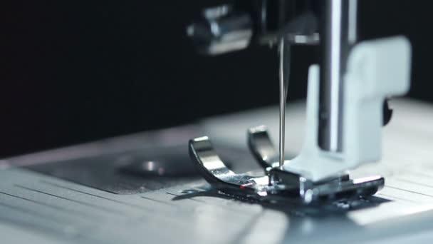 Ocelové šicí jehly v pomalém pohybu. Moderní šicí stroj. Closeup