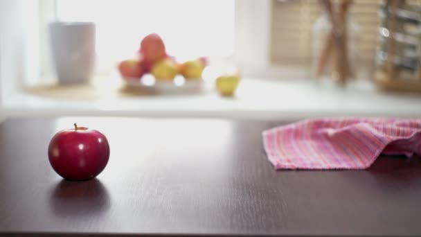 Red apples on wooden table. Hand putting a ripe red apples on a wooden table