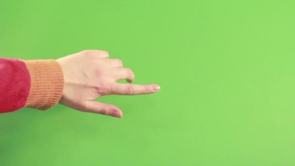 Muž ve studiu izolovaných na zelené obrazovce. Rukou ukázal na pozadí