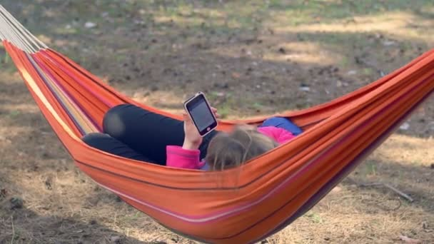 Girl in hammock using smartphone. Young woman surfing internet on mobile phone