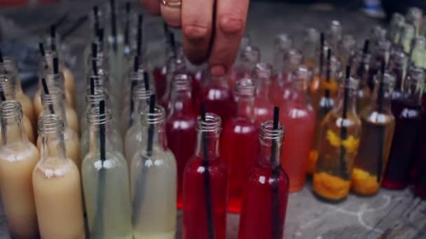 Small liquor bottles. Hand put liquor bottle to other alcohol bottles