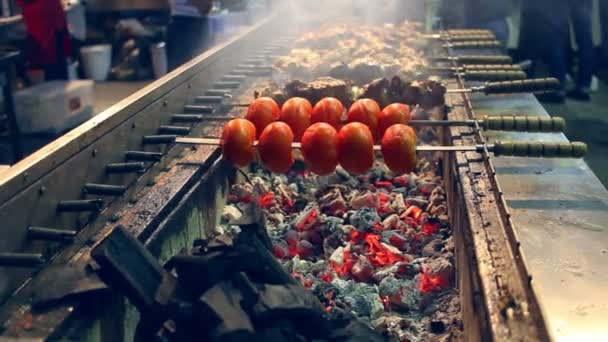 Grilovaná rajčata a maso na špejle. Large mangal na ulici food festivalu