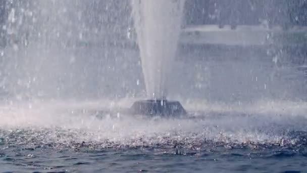 Gocce dacqua che spruzza sulla superficie dellacqua al rallentatore. Fontana di acqua