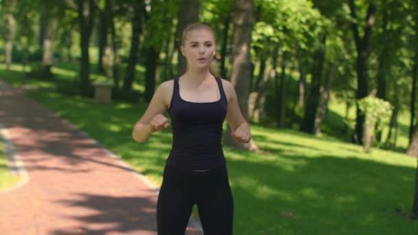 Fitness-Frau im freien Schultern Aufwärmen. Fit Mädchen im grünen park
