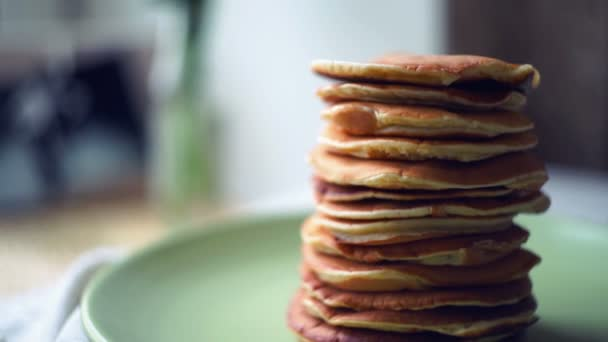 Pancakes stack on green plate at kitchen table. Close up of american pancakes