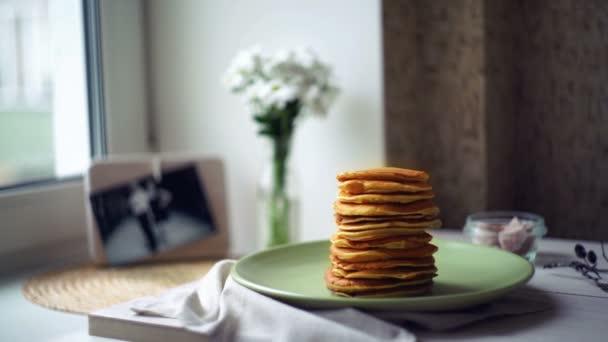 Woman puts pancake from pancake pan on top of pancake stack. Pancakes breakfast