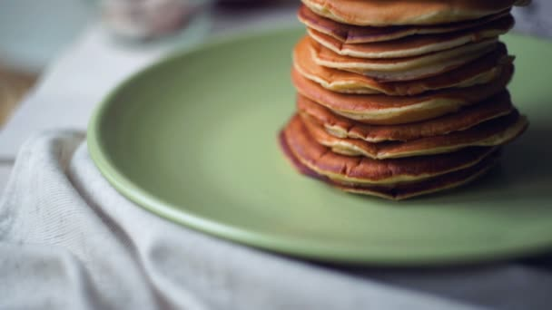 American pancakes. Panning on pancakes stack on green plate at kitchen table