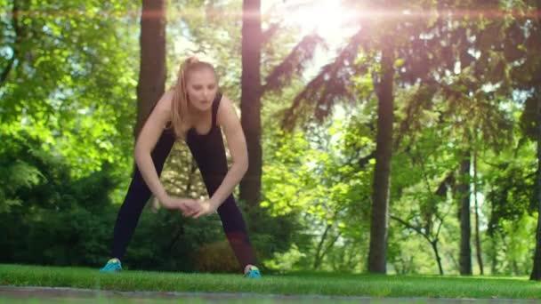 Žena fitness strečink venkovní při východu slunce. Sportovní žena fitness cvičení