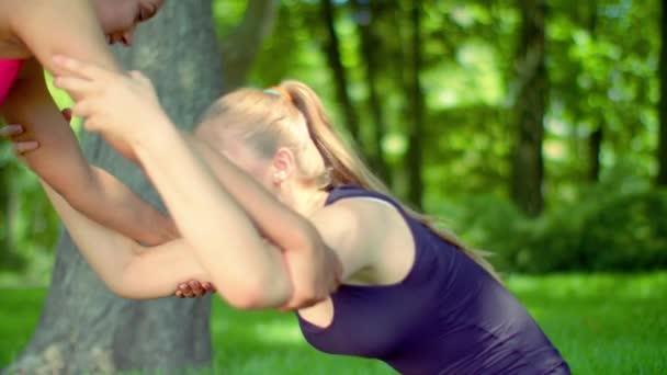 Blond žena strečink s pomocí přítele venkovní. Žena sportovní strečink