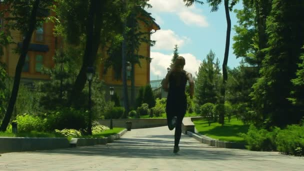 Ženská v pomalém pohybu v parku alley. Ženské běžec běží venkovní