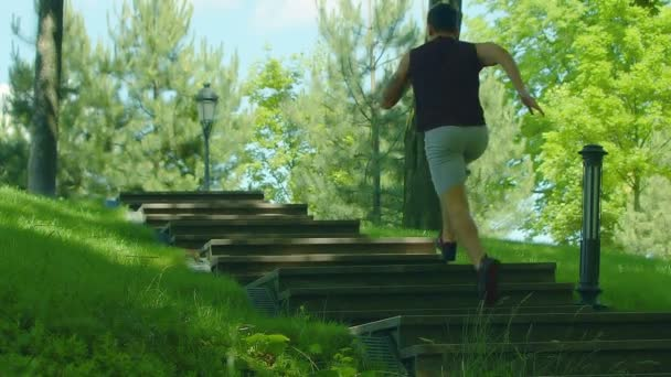 Fitness man run up stairs outdoor. Running man on staircase in slow motion