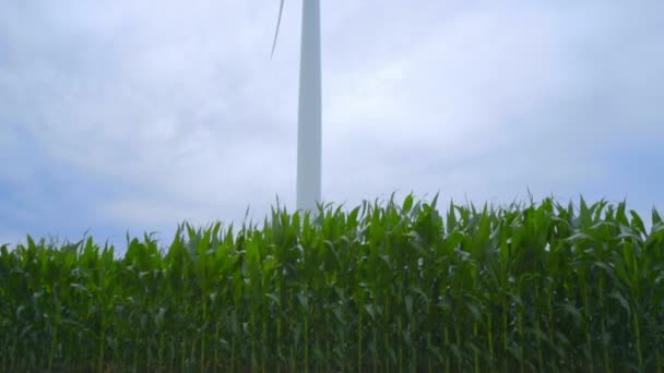 Wind tower against cloudy sky. Closeup of wind turbine on corn field