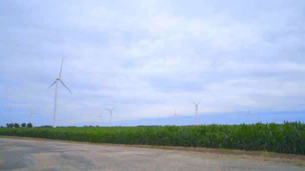 Wind turbines farm. Wind generators landscape. Rustic road under clouds sky