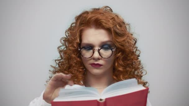 Vážná žena držící knihu v rukou. Zamyšlená dívka otáčí stránky knihy