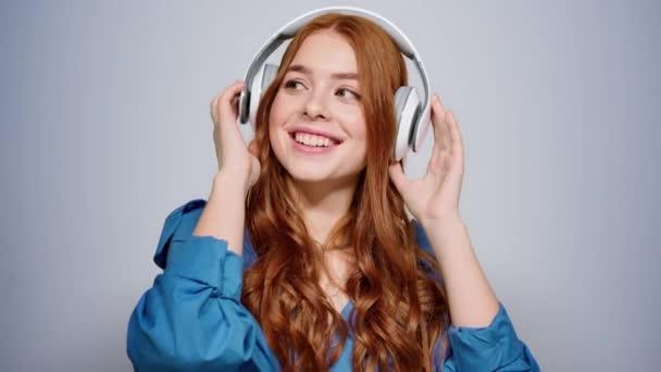 Usmívající se dívka poslouchající hudbu uvnitř. Uvolněná žena dělá pohyby ve studiu