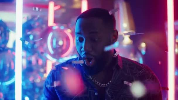 Afroameričan dostává v klubu dobré zprávy. Muž držící telefon na pozadí neonových lamp