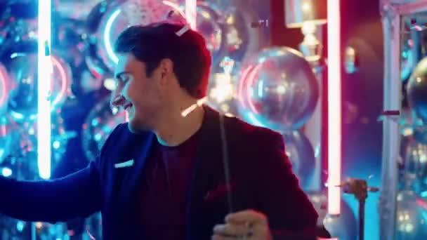 Pozitivní chlap držící jiskry v nočním klubu. Muž tančí pod konfety