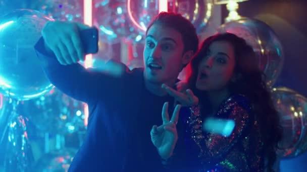 Aranyos pár szelfit készít a nightclubban. Férfiak és nők gesztikulálnak a partin