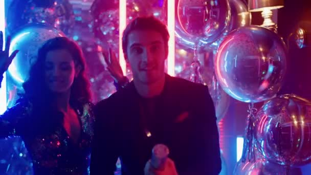 Nettes Paar, das Spaß im Club hat. Mann und Frau öffnen Feuerwerkskörper bei Party