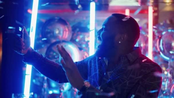 Afroameričan fotí na večírku. Chlápek se znaménkem vítězství konfety