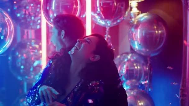 Glückliches Paar lacht im Nachtclub. Mann und Frau tanzen auf Disco-Party