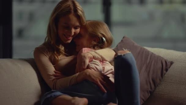 Matka objímající dceru na gauči. Máma a dítě tráví čas spolu doma.