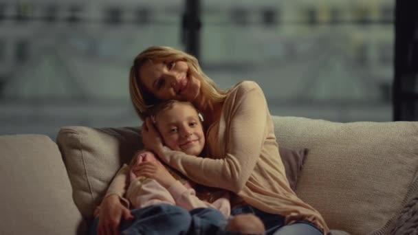 Šťastná matka a dcera objímající se na gauči. Máma a dítě pózují v obývacím pokoji.