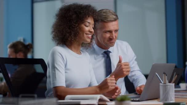 Podnikatel a podnikatelka ukazující palce nahoru během videohovoru na notebooku