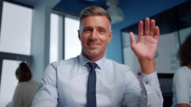 Portrét pozitivního obchodníka mávající rukou před kamerou během online videohovoru