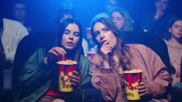 Fiatal nők nassolnak a moziban. Aranyos barátnők pihentető popcorn