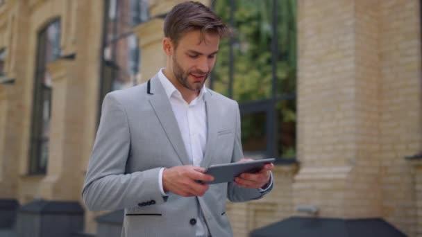 Překvapený muž, který používá tablet v pohybu. Byznysmen čtení zprávy zařízení mimo