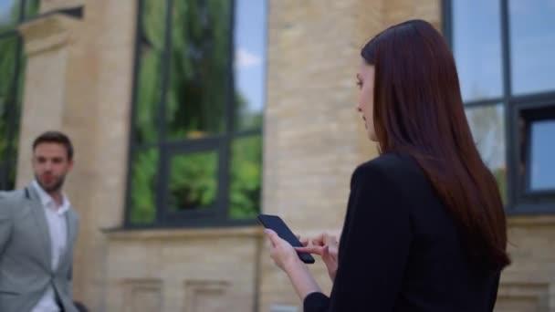 Podnikatelka rolování mobilní telefon venku. Lidé chodící ulici se zařízeními