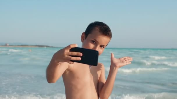 Cheerful boy looking to camera at seashore. Smiling guy taking selfie at beach.
