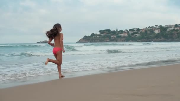 Young woman running at coastline. Carefree girl enjoying holiday at beach.