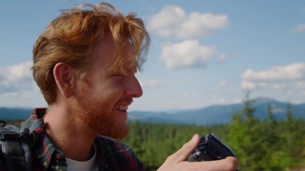 Usmívající se chlap fotografování malebné krajiny na profesionální fotoaparát