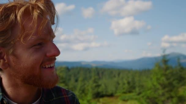 Porträt eines positiven Menschen mit Digitalkamera beim Fotografieren von Bergen