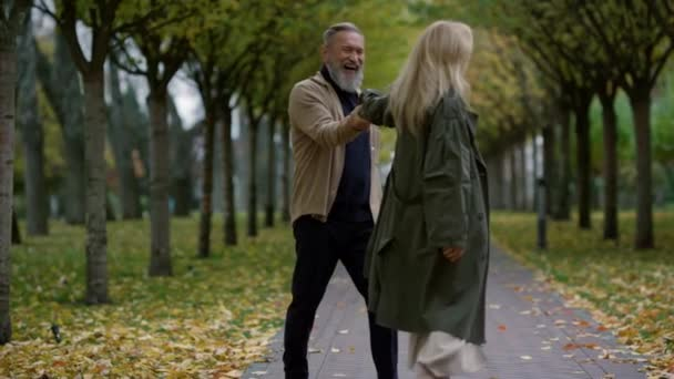 Wide shot of exciting romantic couple having fun in autumn park.