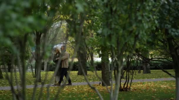 Wide shot of stylish mature couple having walking in autumn nature.