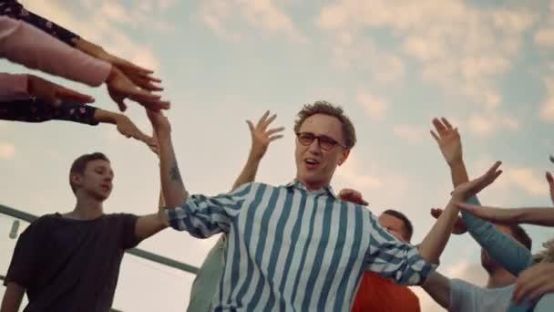 Blízký hipster, co skáče na diskotéce. Párty lidi baví na střeše.