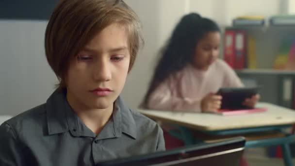 Mosolygó iskolás fiú ül íróasztal digitális tabletta az általános iskolában