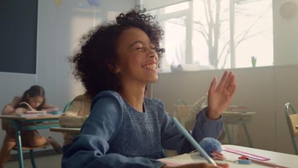 Mosolygó diák kezet emel az órán. Nevető iskolás lány válaszol a kérdésre