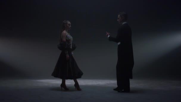 Tanzpaar Händchen haltend auf dunkler Bühne. Mann lädt Frau zum Tanz ein.