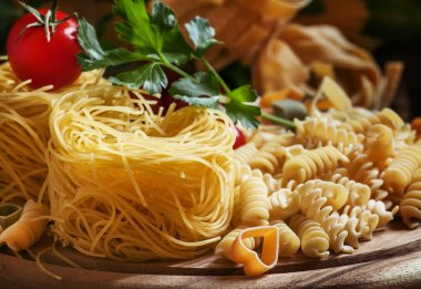Dry Italian pasta Barbine in nests with cherry tomatoes and parsley