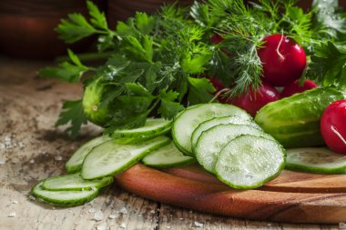 Slices of fresh cucumber, parsley, dill on wooden background